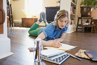Woman drawing on living room floor - p1192m1031715f by Hero Images