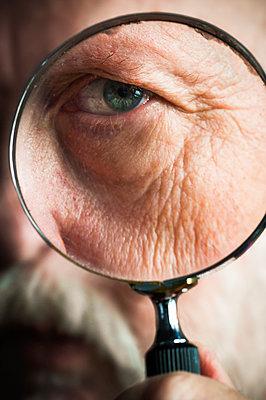 Älterer Mann blickt durch eine Lupe - p1418m2013807 von Jan Håkan Dahlström