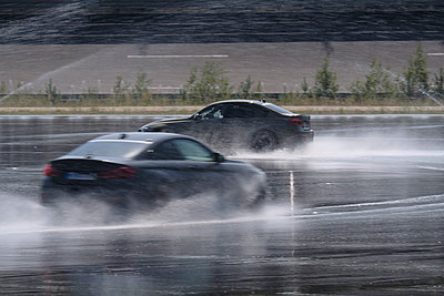 Two cars driving on wet surface on racetrack - p300m2060049 by Hans Mitterer