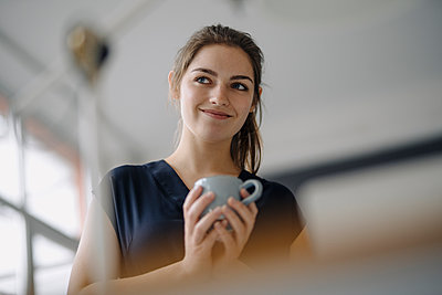 Portrait of smiling young woman with cup of coffee in office - p300m2171100 by Kniel Synnatzschke