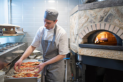 Chef putting tomato sauce onto Pinsa Romana, a Roman style pizza blend reducing sugar and saturated fat, containing rice and soy with less gluten - p429m2077962 by Monty Rakusen