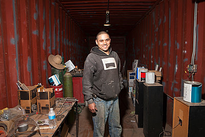 Portrait of builder in shipping container looking at camera smiling - p924m1422751 by Raphye Alexius