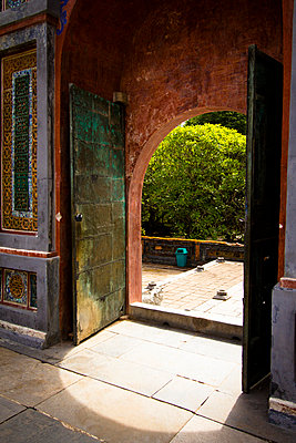 A colourful gate inside Tu Duc tomb, Thua Thien Hue, Vietnam, Asia 2012. Rusty metallic doors are opened to a red arch. - p934m832457 by Francis Roux photography