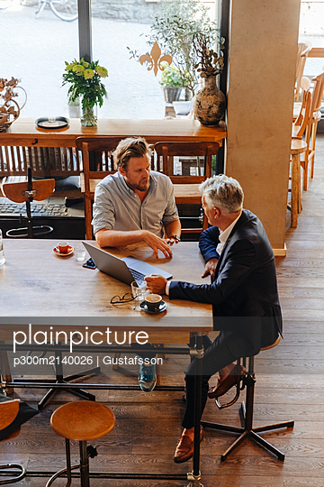 Two businessmen with laptop meeting in a cafe - p300m2140026 by Gustafsson