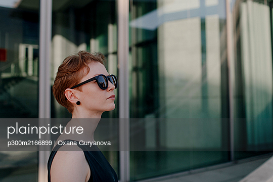 Elegant red-haired woman with sunglasses in the city, portrait - p300m2166899 by Oxana Guryanova