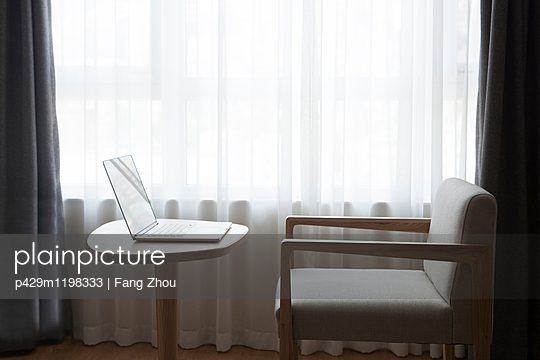 Laptop on desk with chair, in front of window - p429m1198333 by Fang Zhou