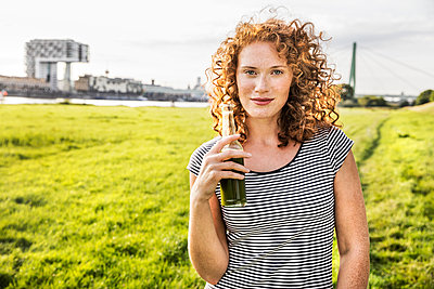 Germany, Cologne, portrait of redheaded young woman with beverage - p300m2069826 by Jo Kirchherr