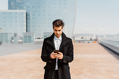 Businessman using cell phone in the city - p300m2102255 by VITTA GALLERY