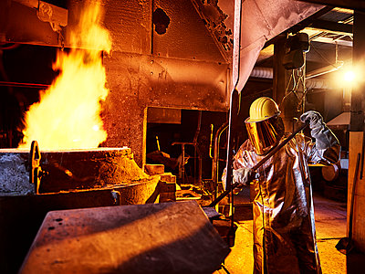 Worker holding metal rod in furnace at foundry - p300m2139727 by Christian Vorhofer