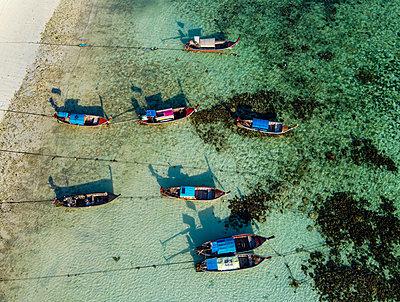 Thailand, Satun Province, Ko Lipe, Fishing boats moored at shore of coastal beach - p300m2203081 by Michael Runkel