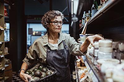 Mature male entrepreneur arranging product on rack at delicatessen store - p426m2270531 by Maskot