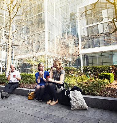 Businesswomen sitting on wall for coffee break - p429m803586f by Liam Norris
