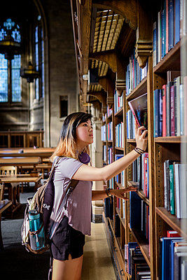 Chinese woman standing in library choosing book - p555m1301985 by Take A Pix Media