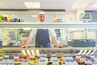 Caucasian butcher smiling behind counter in shop - p555m1410357 by Dave and Les Jacobs