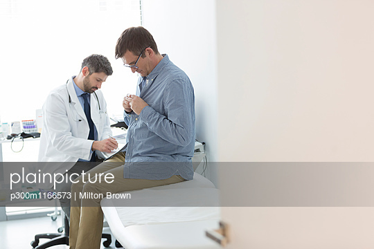 Doctor with patient in examination room - p300m1166573 by Milton Brown