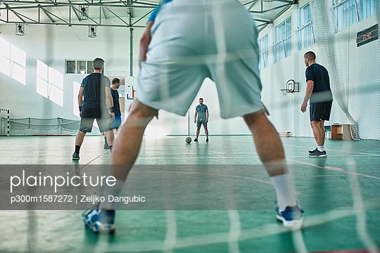 Men playing indoor soccer - p300m1587272 von Zeljko Dangubic