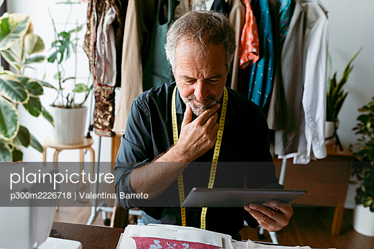 Mature male tailor thinking while looking at digital tablet in work studio - p300m2226718 by Valentina Barreto