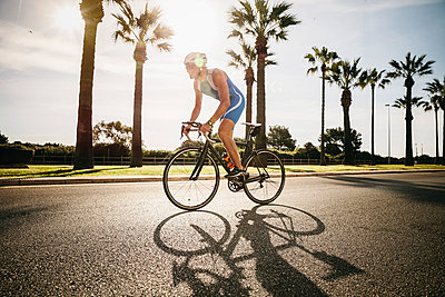 Spain, Mallorca, Sa Coma, triathlet training on bicycle - p300m1028862f by Mareen Fischinger