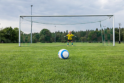 Young football goalkeeper with ball on football ground - p300m1580973 by Fotoagentur WESTEND61