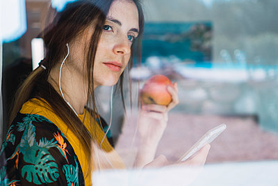 Young woman with earphones, cell phone and apple looking out of window - p300m1581323 by Kike Arnaiz