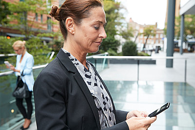 Businesswoman using mobile phone with colleague standing in city - p300m2227079 by Pete Muller