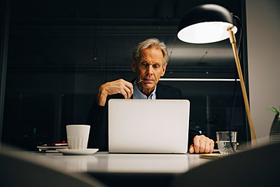 Dedicated senior male entrepreneur looking at laptop while working late in creative workplace - p426m2194717 by Maskot