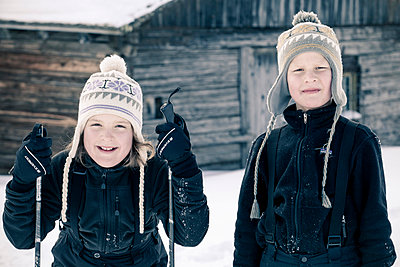 Portrait of little girl holding ski poles while standing with brother - p426m803207f by Katja Kircher