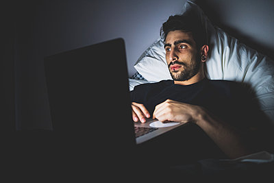 Bearded young man lying in bed at night, looking at laptop.  - p429m2201950 by Eugenio Marongiu