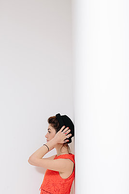 Female model in an orange dress leaning against a white wall. - p686m1124871 by Paul Tait