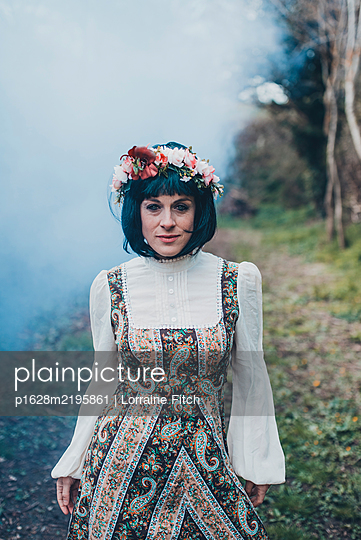 Woman with black bob and flower crown dancing in field - p1628m2195861 by Lorraine Fitch