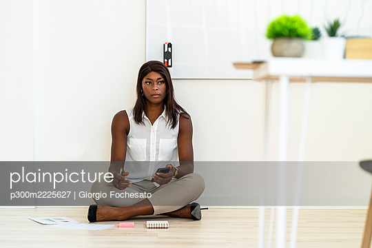 Businesswoman using mobile phone while sitting on floor at office - p300m2225627 by Giorgio Fochesato