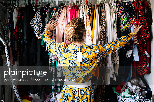 Fashionable blond woman in new yellow dress choosing from clothes rack at apartment - p300m2242855 by Jose Luis CARRASCOSA