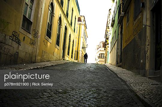 Man on cobbled street - p378m921900 by Rick Senley