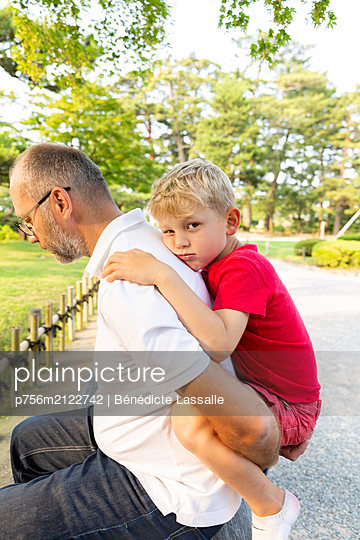 Father gives son a piggyback ride - p756m2122742 by Bénédicte Lassalle