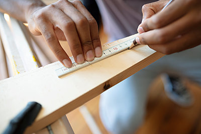 Close up man doing DIY carpentry project, measuring and marking wood - p1192m2016699 by Hero Images