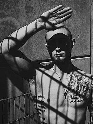 Man with tattoos on bare chest protects himself from the sun - p1267m2263399 by Jörg Meier