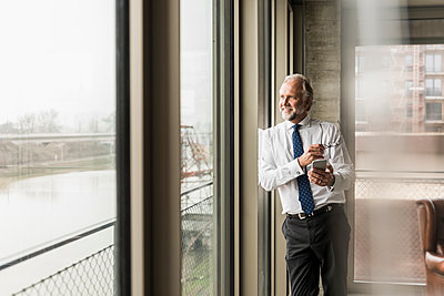 Smiling mature businessman standing at the window looking out - p300m1563202 by Uwe Umstätter