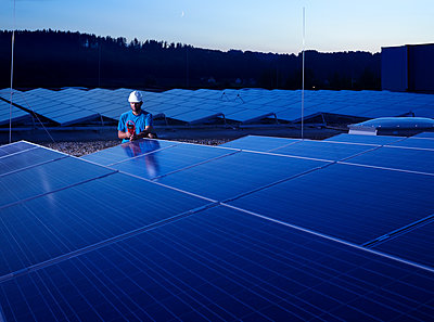 Worker with measuring device checking solar plant in the evening - p300m1586966 by Christian Vorhofer