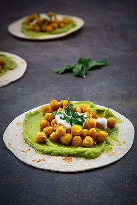 Pita-Brot mit Avocado-Creme, Kurkuma-Kichererbsen, Joghurt-Sauce und Petersilie - p300m2144361 von Larissa Veronesi