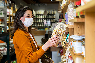 Young woman in protective face mask checking food package while shopping at grocery store - p300m2264464 by VITTA GALLERY