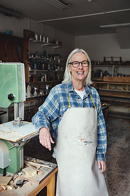 Portrait of smiling senior owner standing by machinery at workshop - p426m1543019 by Maskot