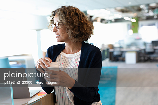 Mature businesswoman in modern office with coffee cup - p1192m2123300 by Hero Images