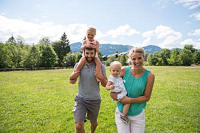 Junge Familie mit zwei Töchtern spazieren auf Wiese - p1142m2109460 von Runar Lind