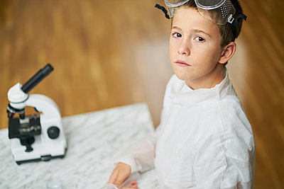 young boy looks at camera dressed in white coat prepares to observe by a microscope at home and do experiments - p1166m2153905 by Cavan Images