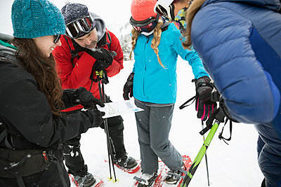 Family snowshoeing, checking map - p1192m1546638 by Hero Images