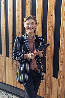 Portrait of happy businesswoman with digital tablet outdoors - p300m2203123 by A. Tamboly