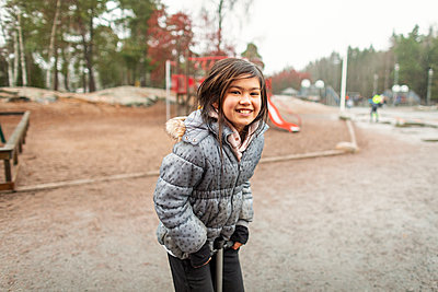Happy girl on pogo stick looking at camera - p312m2191282 by Scandinav