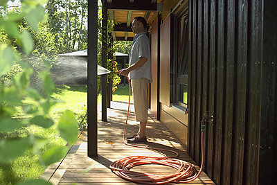 man standing on veranda of weekend home watering the lawn - p3160547f by BreBa photography