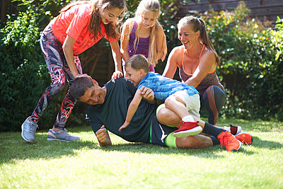 Family playing in garden - p429m1504733 by Peter Muller