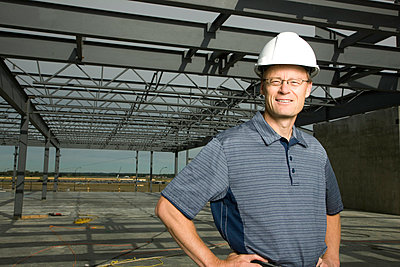 Man with a hard hat standing by building under construction - p4428390f by Design Pics